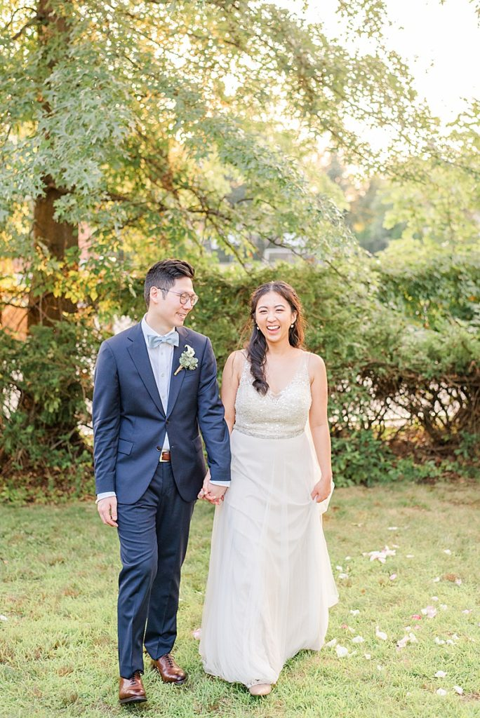 bride and groom walk through yard at sunset