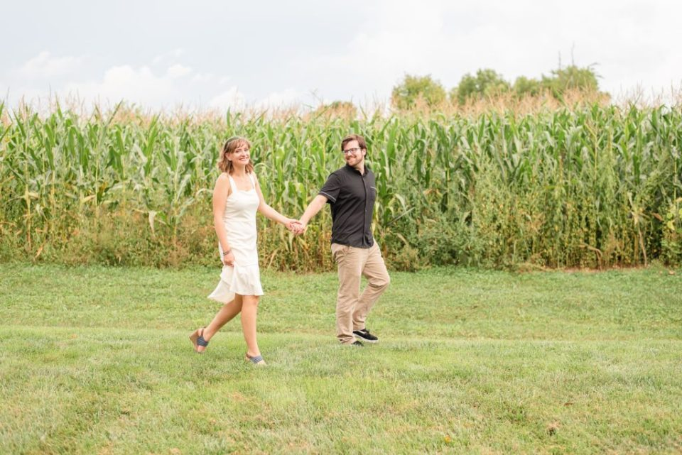 couple walks through field at Historic Stonebrook Farm