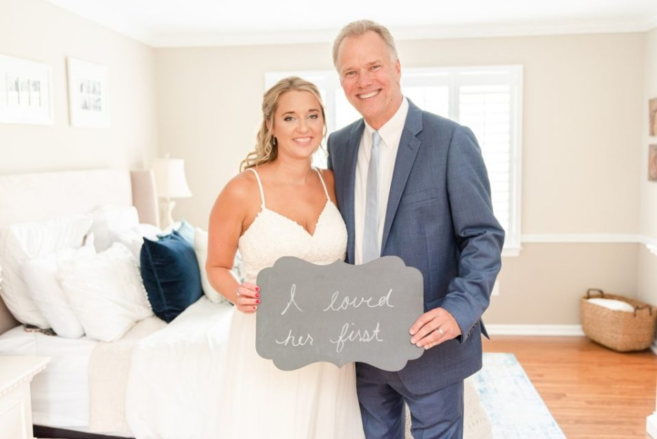 "bride and dad pose with sign that says ""I loved her first"""
