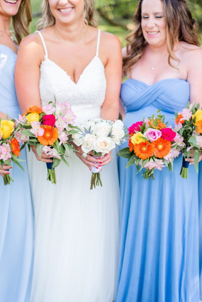 bridesmaids hold pink and orange flowers