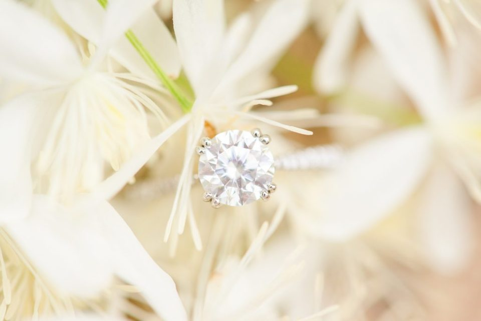engagement ring sits on white flowers