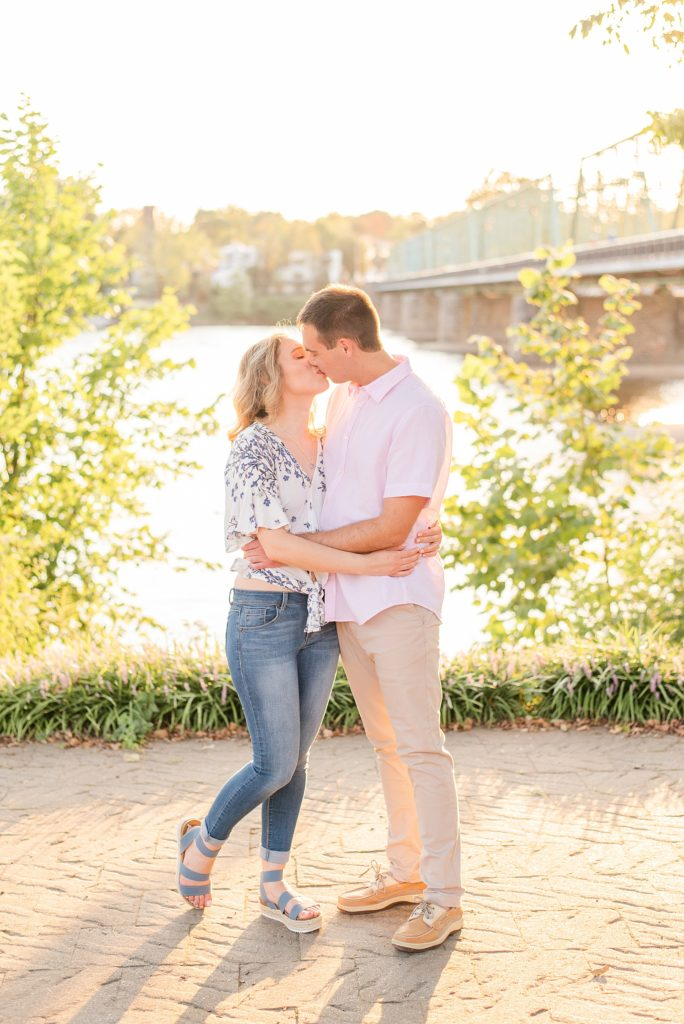 engaged couple kisses by water in New Hope PA