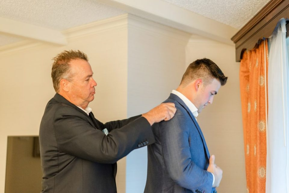 dad adjusts collar on groom's jacket