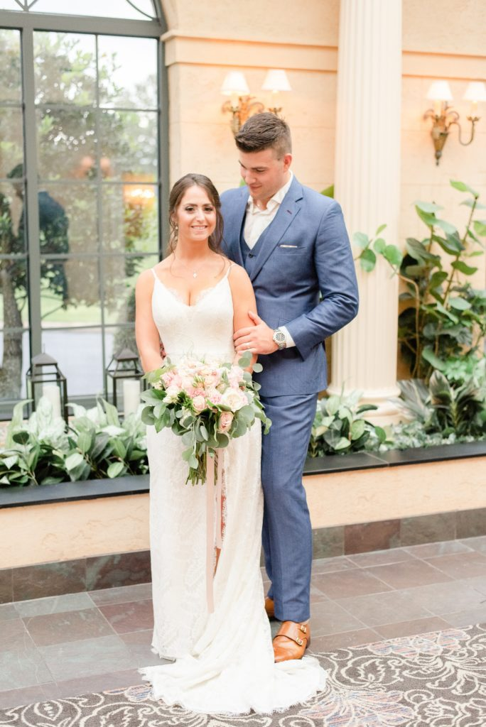 groom hugs bride from behind during wedding photos