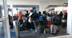 folks sitting down and taking off shoes in boarding area dfw airport renespoints blog
