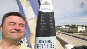 renespoints-infront-of-surf-board-with-arrival-flights-sxm-sunset-bar