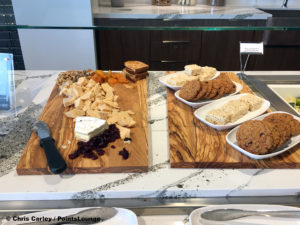 A cheese board with cranberries, walnuts, and dried apricots is displayed next to a selection of desserts at the Delta Sky Club Austin airport lounge in Austin, Texas. Photo © Chris Carley / PointsLounge