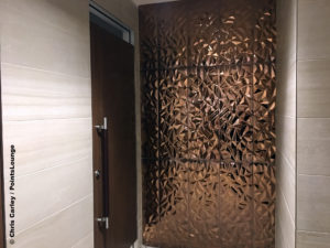 Copper artwork is seen inside the men's restroom at the Delta Sky Club Austin airport lounge at Austin-Bergstrom International Airport (AUS) in Austin, Texas. Photo © Chris Carley / PointsLounge