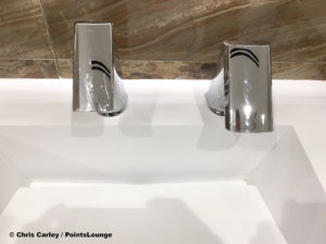 A sink, faucet, and motion activated hand dryer are seen inside the men's restroom at the Delta Sky Club Austin airport lounge at Austin-Bergstrom International Airport (AUS) in Austin, Texas. Photo © Chris Carley / PointsLounge