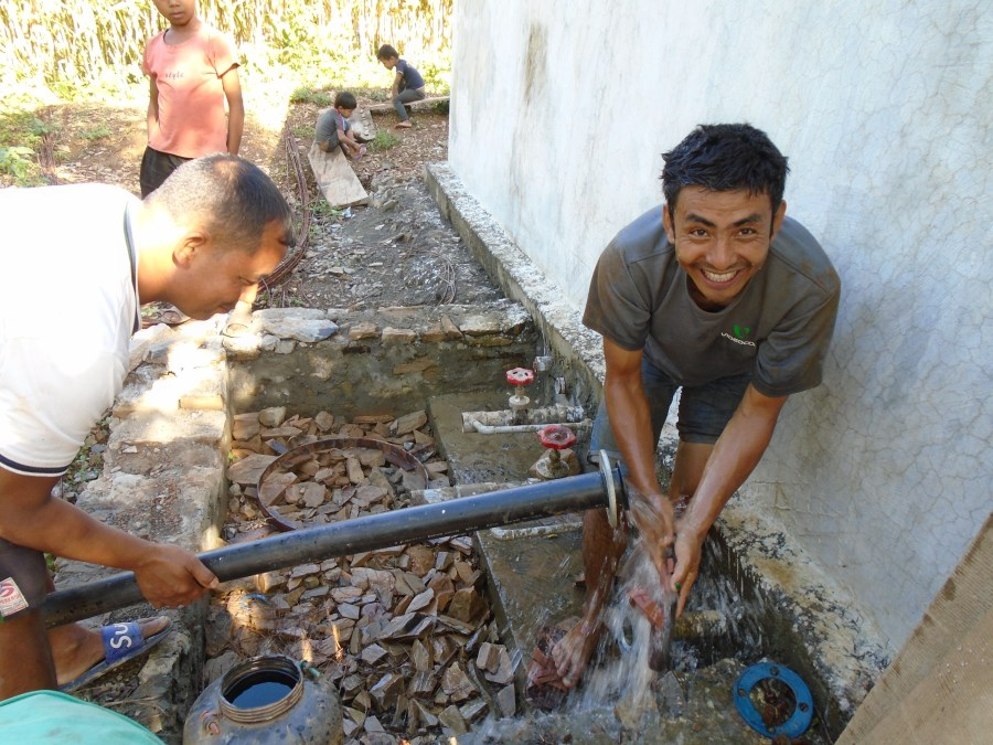 a man washing his hands with water from the newly installed solar water pumping system