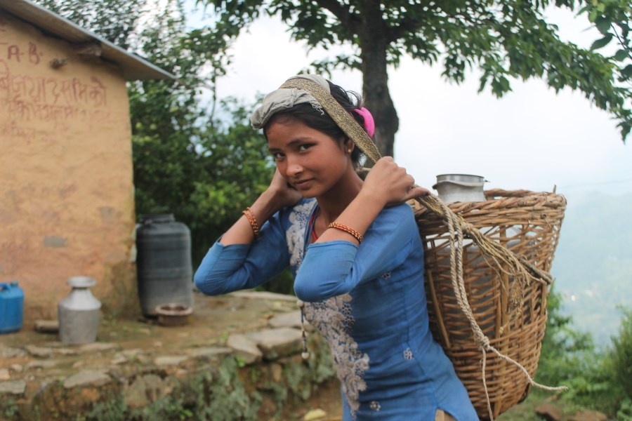 Young Nepali woman carrying a basket on her back with a large vessel of water