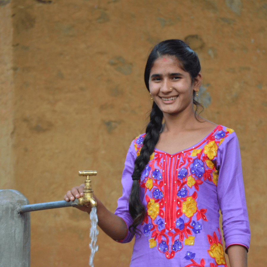 a woman in Nepal with water sourced with a solar multi-use system