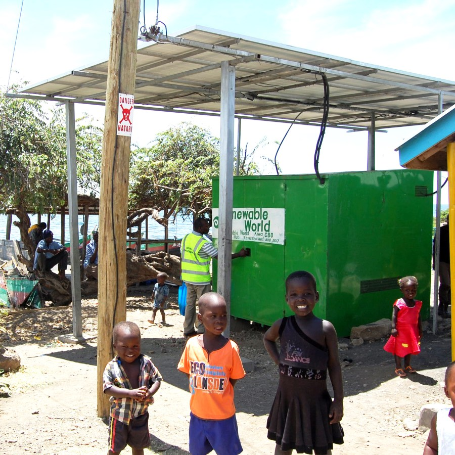 children stood in front of a type of renewable technologies - solar microgrids