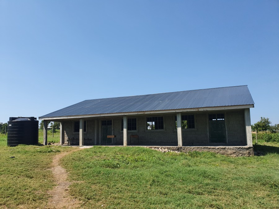 A very basic school building pictured from the outside. Bright blue sky overhead and a dirt path leading up to the classrooms.