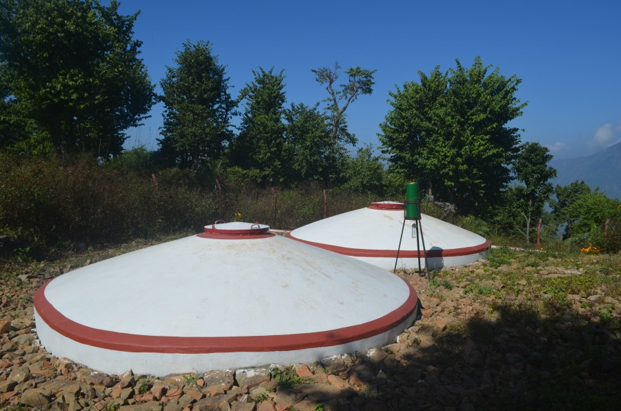 The two round water storage tanks, painted white with red trim.