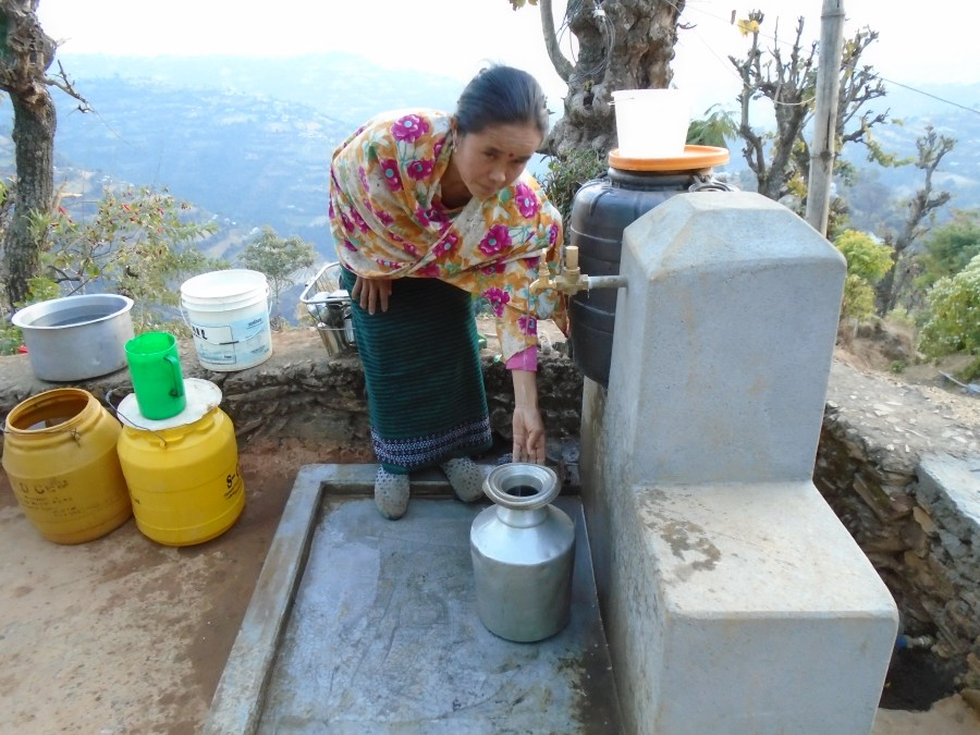 Maya Reshmi collecting water from the new tap stand outside her home
