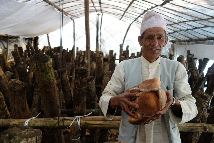 A Sirubari man holding locally grown food.