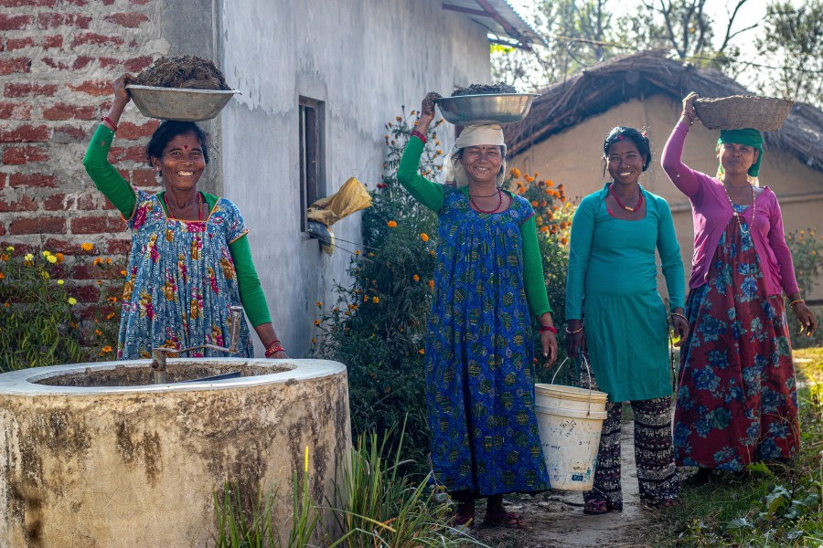Four smiling Nepali women, three of them are carrying items on their head, one a bucket in her hand. All are benefitting from a Renewable World biogas project.