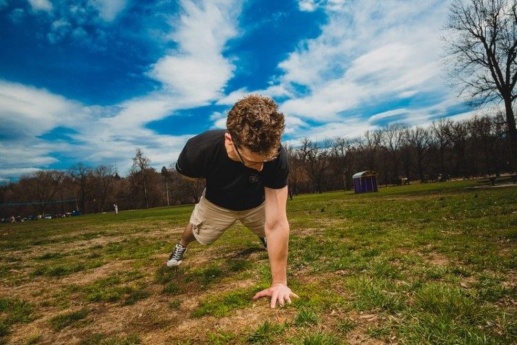 man doing a one-arm pushup outside in a field