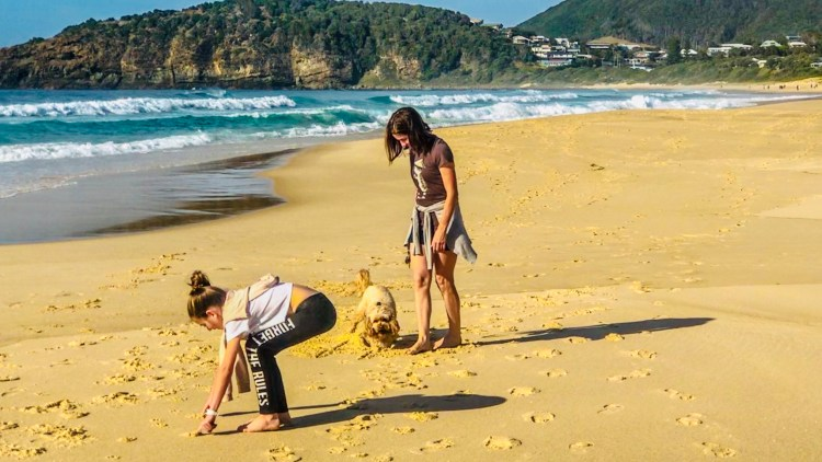mother and daughter on the beach with a dog