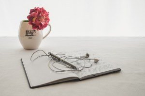 flower, journal, earbuds, pen, cup
