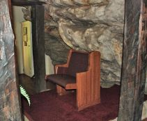The Inside the church, the boulder extends over the Pastor's pew.