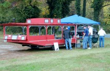 A caboose-style trailer features an operating model railroad display.