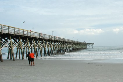 A couple pauses to watch the surf roll in by the pier.