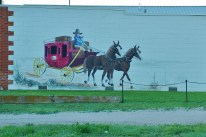 Stagecoach art on a building across the street from the park.