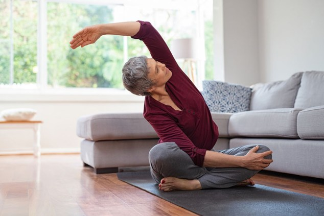 Senior,Woman,Exercising,While,Sitting,In,Lotus,Position.,Active,Mature