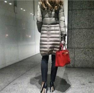 赤いバッグを持ったお姉さんがヘルノを着ている後ろ姿