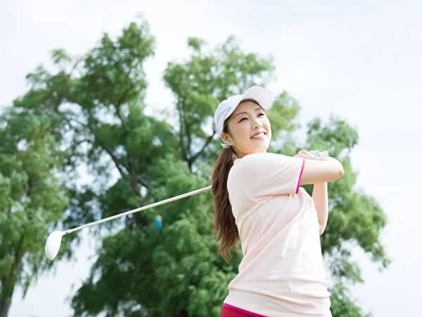 ゴルフ場でスイングをする女性