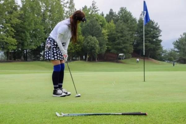 グリーン上でパッティングをする女性ゴルファー