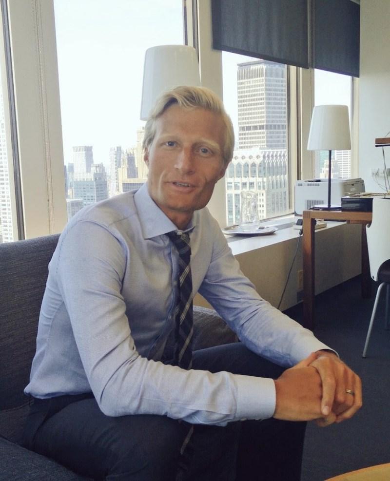 Porträtt på Carl Skau på Svenska FN-reppen, som sitter framåtlutad i en soffa på 46:e våningen med utsikt över Manhattan. Carl har på sig en ljusblå skjorta, mörkblå byxor och en slips lite löst knuten runt halsen.
