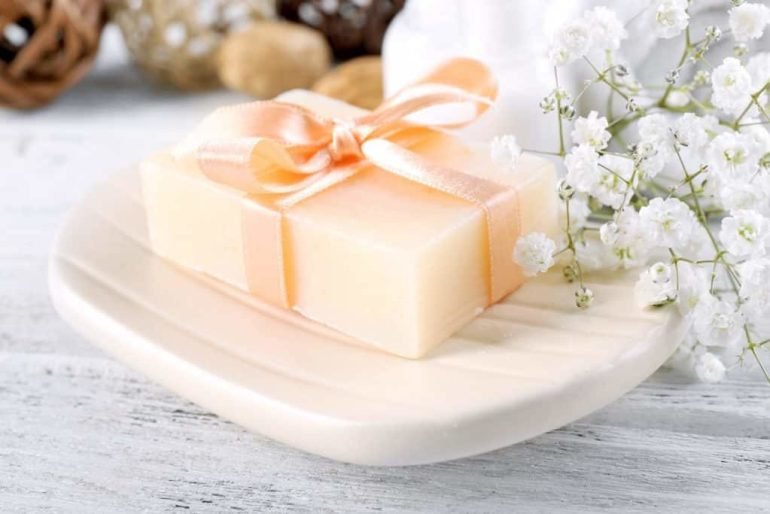 Soap with ribbon on a dish over wooden background, close up