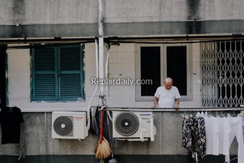 man looking at air conditioner