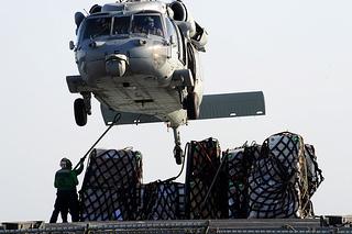 An MH-60S picks up supplies at sea.