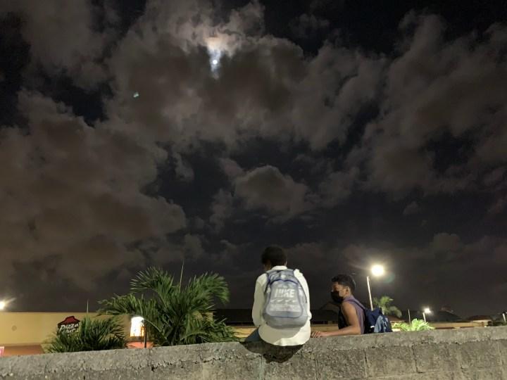 Jóvenes migrantes conversan sentados en el cerco que rodea la terminal de buses De San Pedro Sula. Foto: Dennis Arita