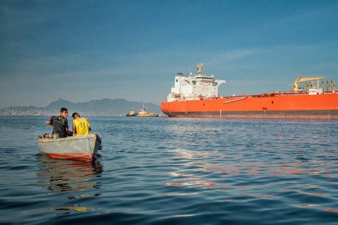 Barco de moradores locais em frente a navio petroleiro. Foto: Marcio Isensee e Sá