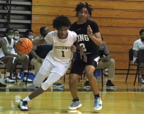 Southwest DeKalb's Xzaviah Taylor (1) drives the baseline against M.L. King's Kaleb Brown (2) during the Panthers key Region 5-5A 50-44 win. (Photo by Mark Brock)