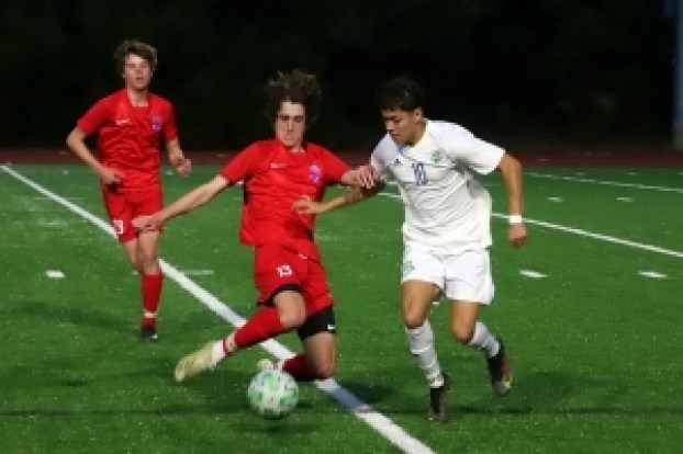 Dunwoody's Nate Lambert (13) battles Discovery's Justin Acosta (10) during first half action of Discovery's 2-0 7-7A boys' win. (Photo by Mark Brock)