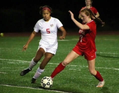 Dunwoody's Sarah Holland (5) battles Druid Hills Reese Rathur (7) for the ball during Dunwoody's 10-1 win on Friday night. (Photo by Mark Brock)
