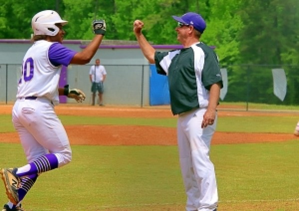 Lakeside's Zaylan Washington (left) gets a fist bump from Coach Brian Granger after his towering home run into the trees in the second inning of the Vikings playoff loss to Lee County. (Photo by Mark Brock)