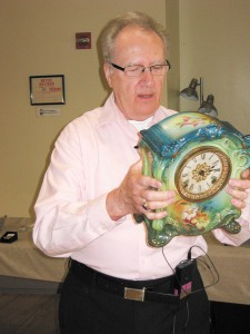 """Appraiser Vernon Abrams inspects a clock during the """"Antiques Roadshow""""-style appraisals at the Dorothy Benson Center."""