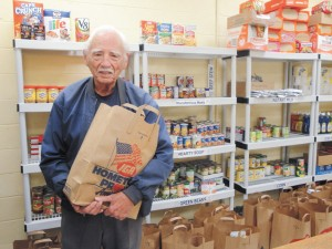 Julius Wallis, left, stocks shelves at the food pantry at the new Suthers Center for Christian Outreach. He and his wife, Deloris, at far left, founded the food pantry.