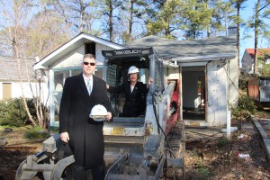 City Manger John McDonough and Mayor Eva Galambos pose with a bulldozer on Feb. 21 in front of a house the city will demolish to make way for a road.