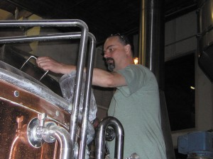 Randy Dempsey, once a home beer brewer, stirs boiling grain in the mashtun in Sandy Springs.