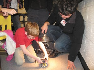 Tarrek Shaben, right, holds a lamp to mimic the sun, in an effort to harness energy for David Walston's solar powered car. Woodland Elementary fourth graders worked with the North Springs Charter High School's robotics team to build the vehicles.