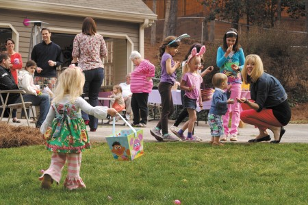 Far left, Peyton Koetje, with other neighborhood children, center, from left, Lucy Johnson, Iris Williams, Annie Quinn and Bennett Brown, are eager to share their findings with Ashley Koetje, far right, during Woodsong Court's Easter festivities on March 30.