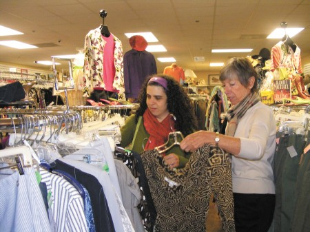 Shopper Elizabeth Valera, left, looks through clothes with Lynn Farrell, a store volunteer and member of the Assistance League of Atlanta, at Attic Treasures Thrift Shop in Chamblee.  The league helps approximately 40,000 local families every year.